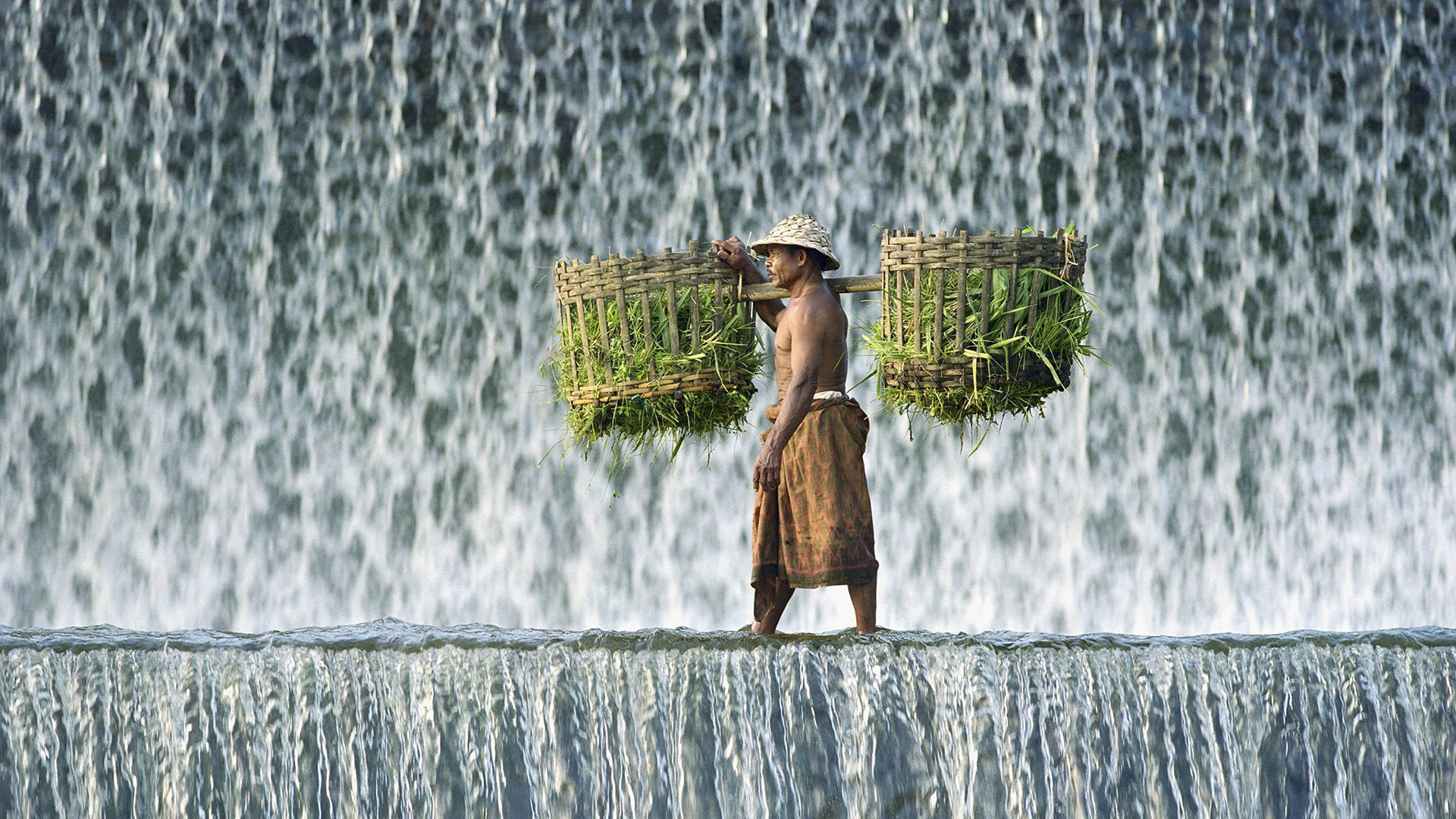 Man Carrying Baskets Of Animal Fodder Past Waterfall