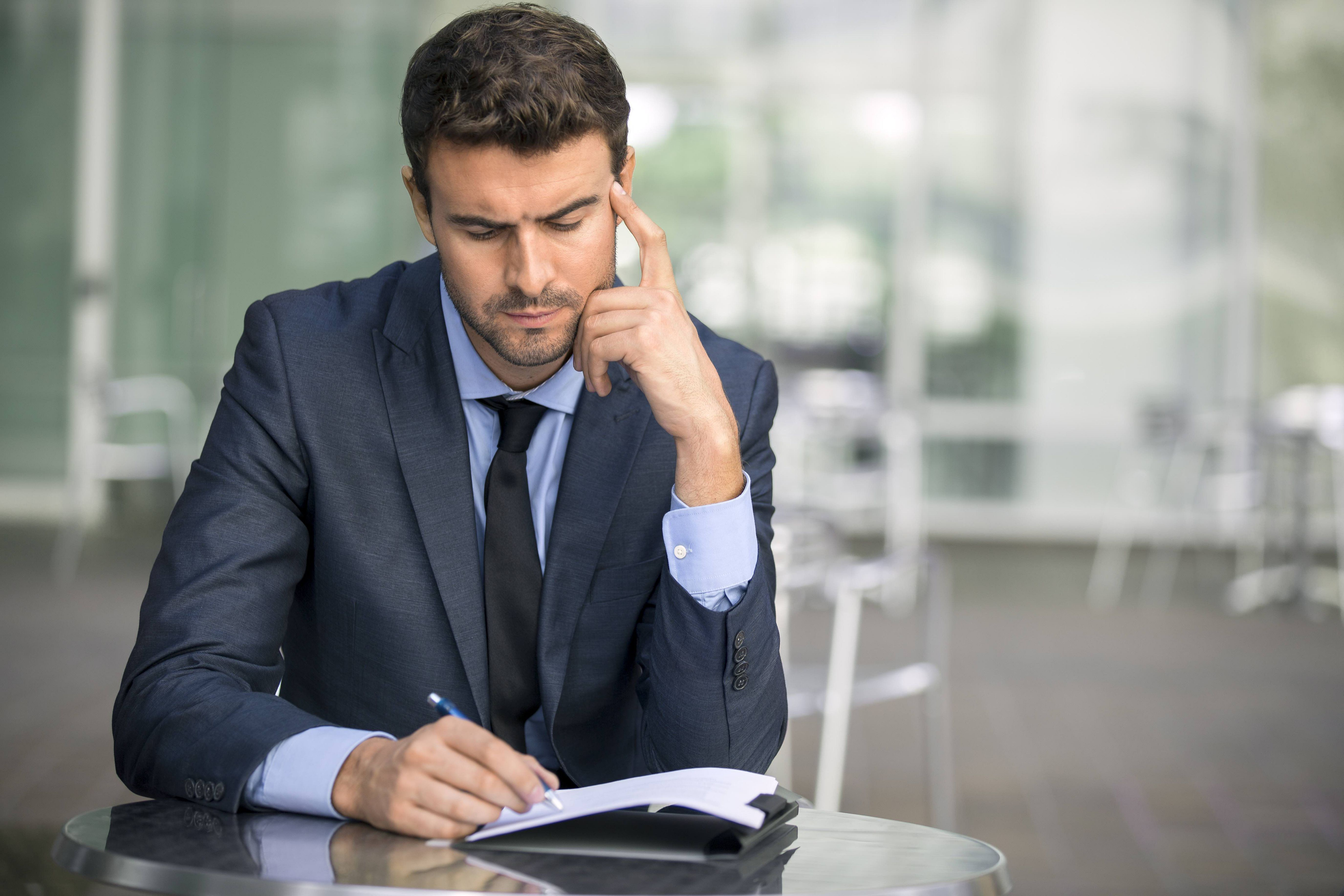 Focused Businessman Thinking And Writing Outside Office